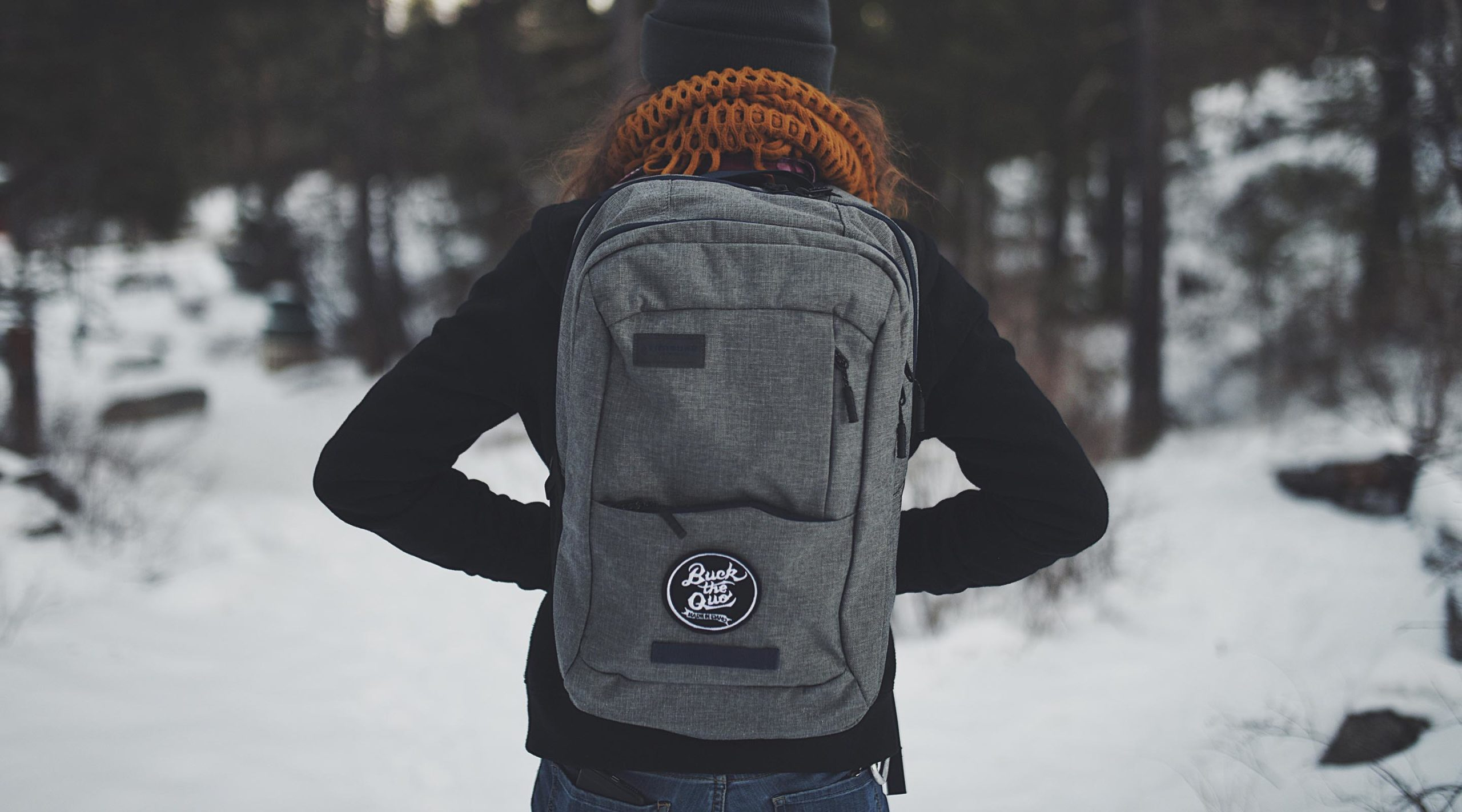 Girl wearing gray backpack with Buck the Quo patch