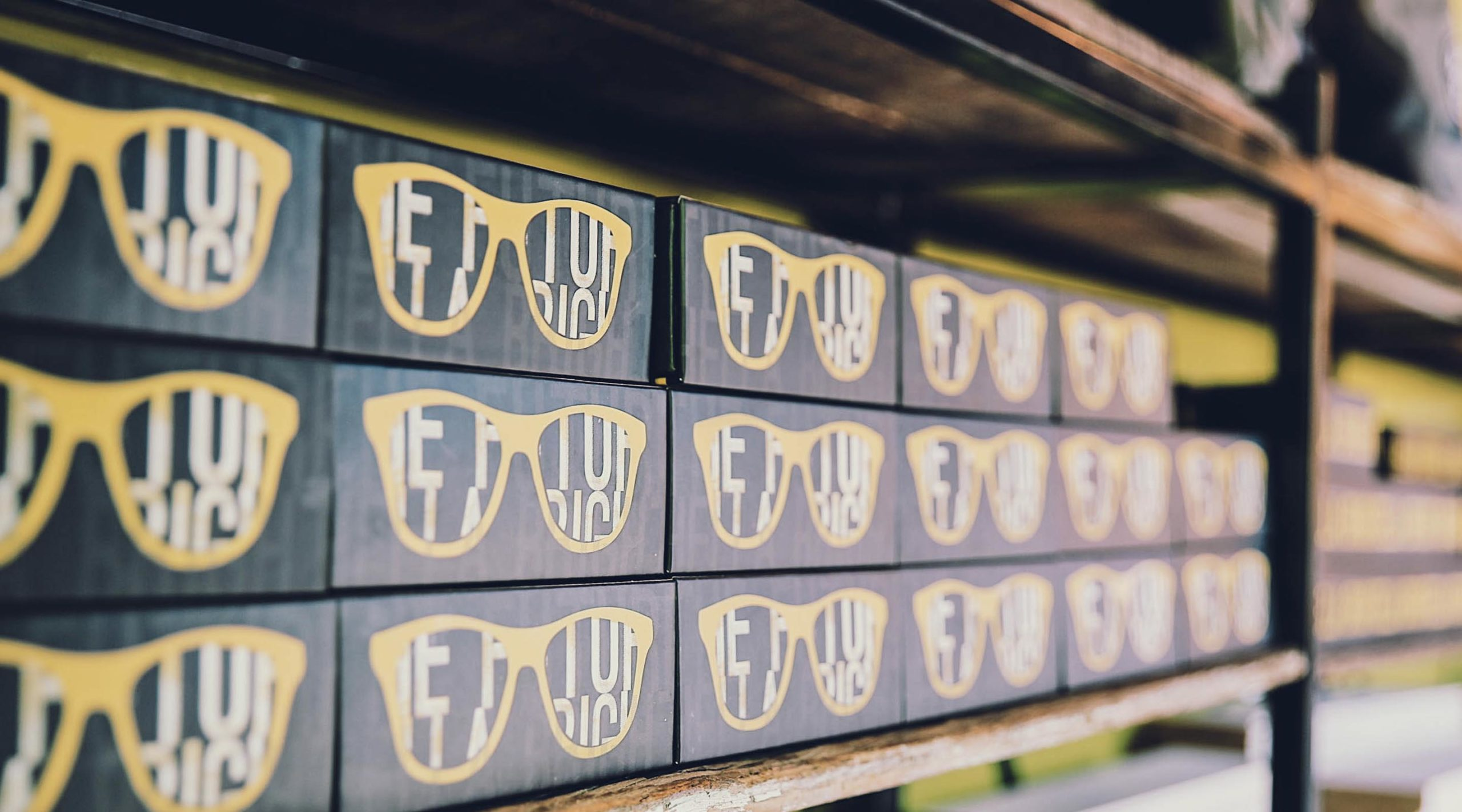 Shelf with rows of black boxes with yellow sunglasses printed on them