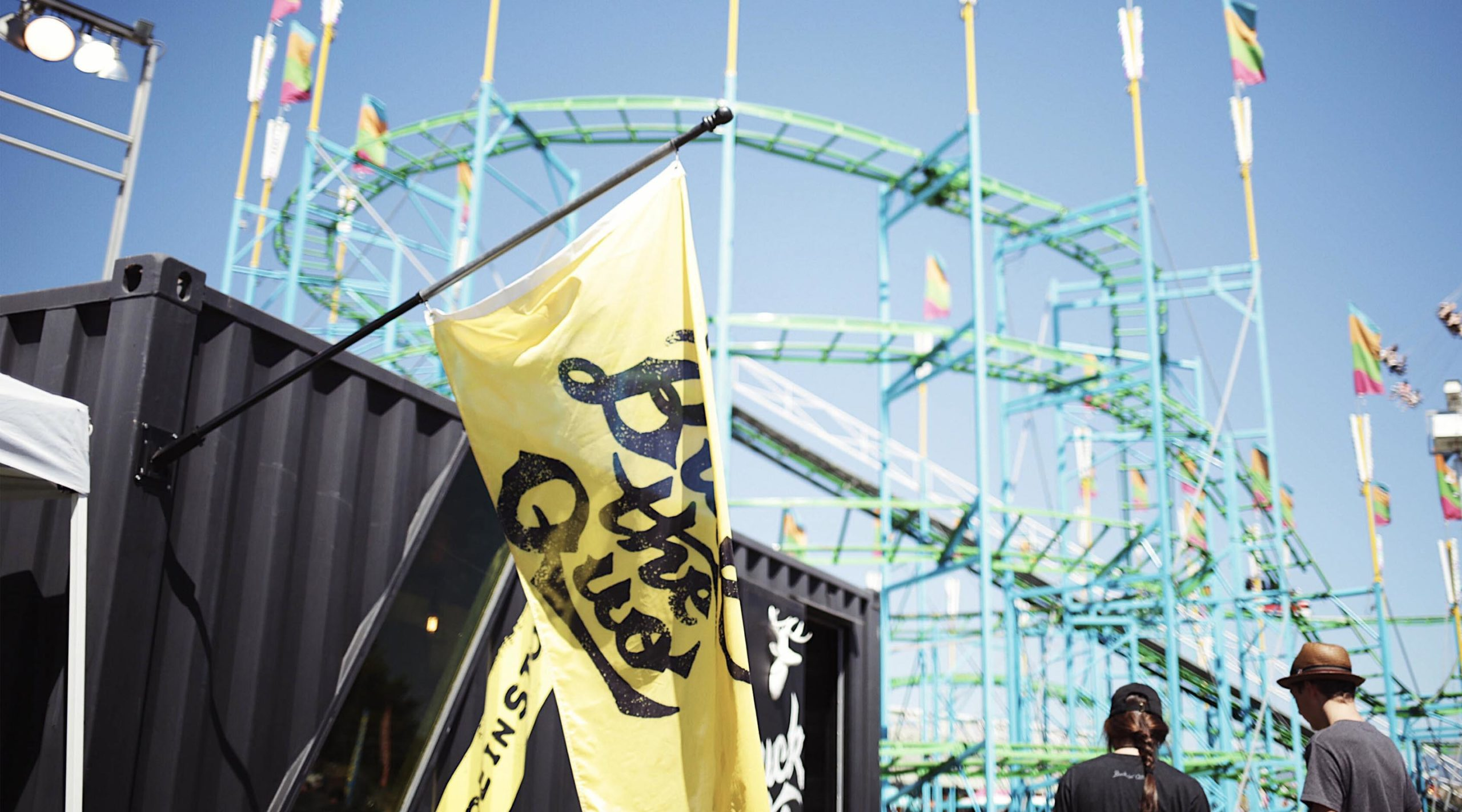 Yellow Buck the Quo flag hanging from black shipping container in front of rollercoaster