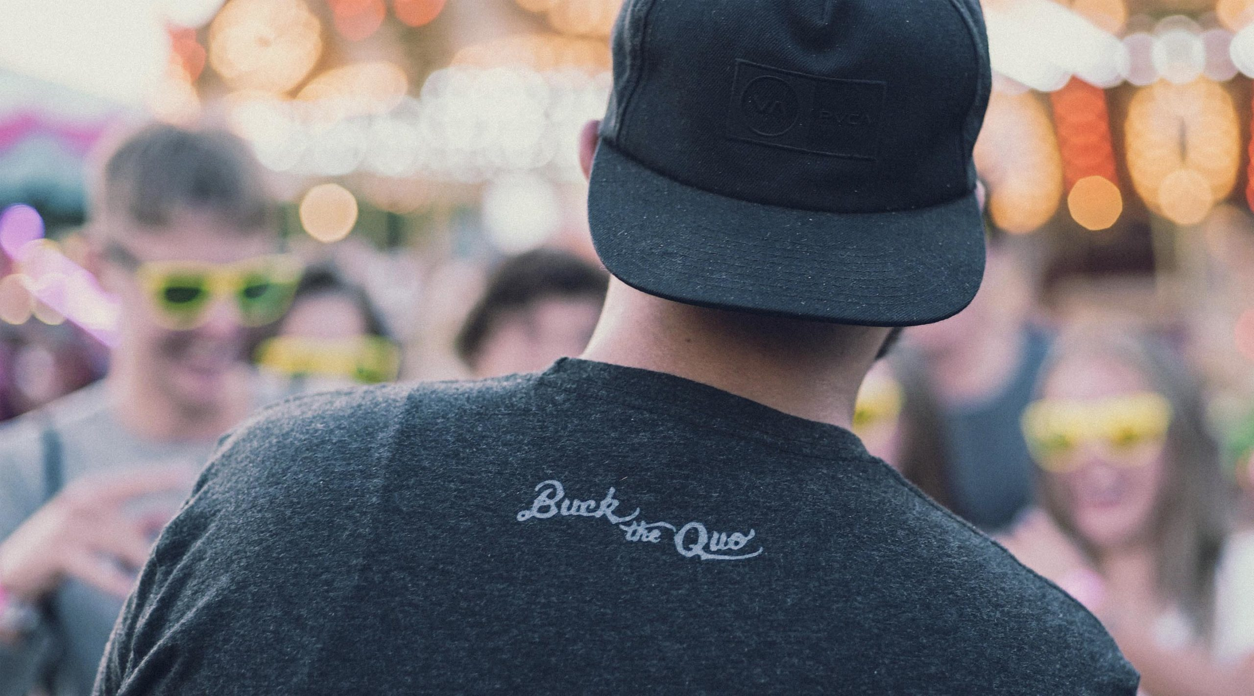Man with backwards cap and black tee with small Buck the Quo logo on back