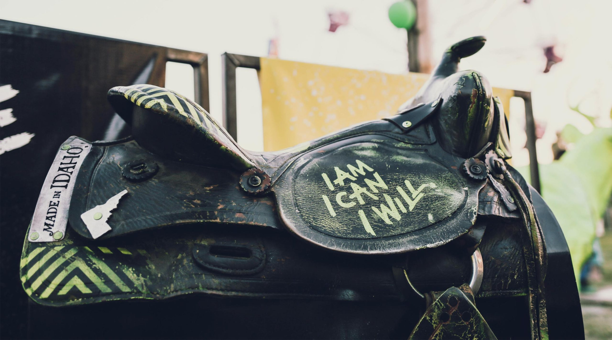 Black saddle with I AM, I CAN, I WILL painted on it in yellow