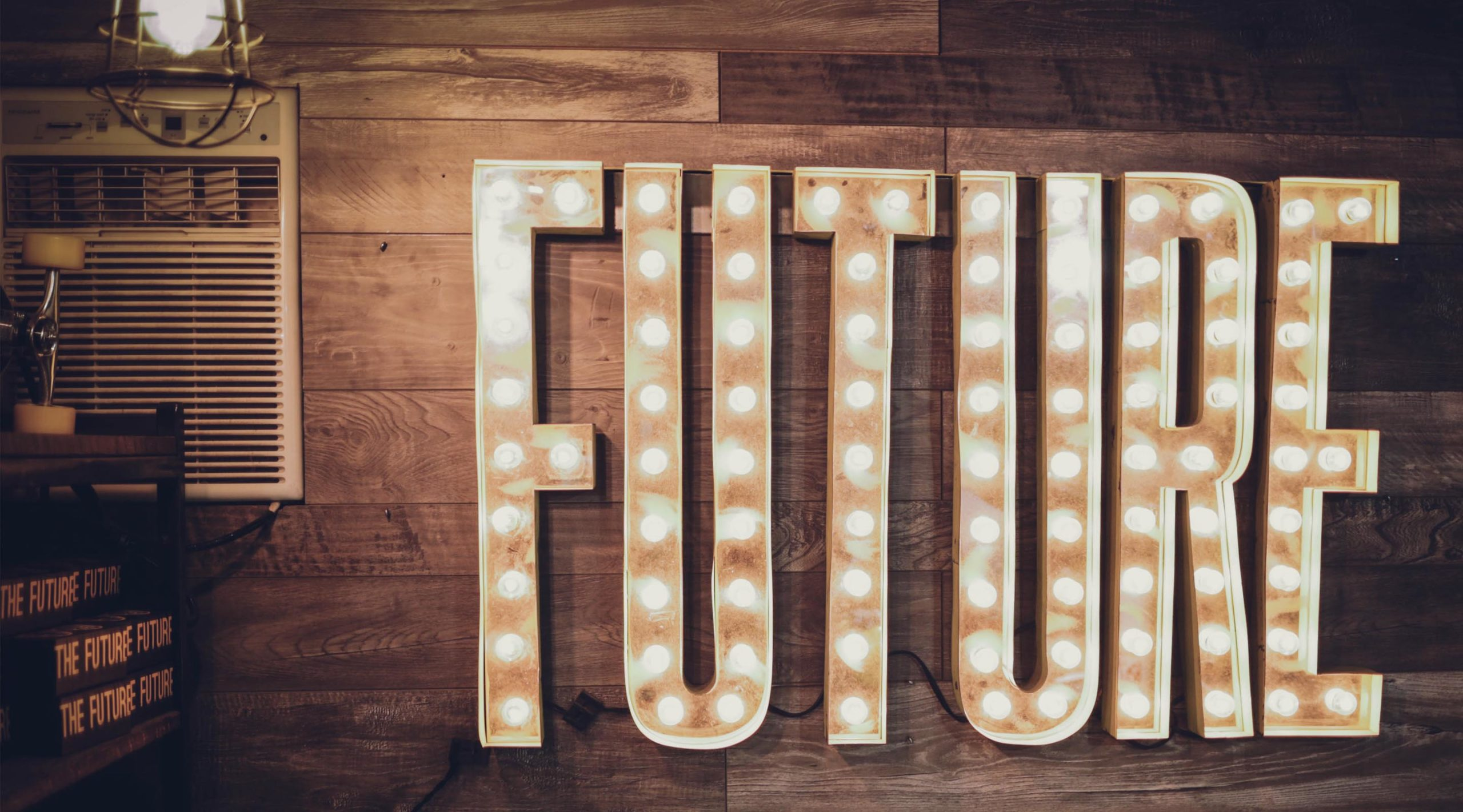 Light up sign that reads FUTURE on wood panel wall