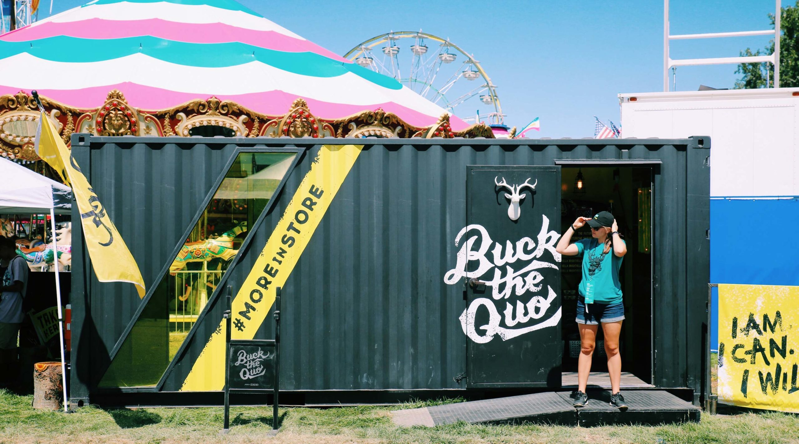 Front of BTQ shipping container with pink tent and ferris wheel in background